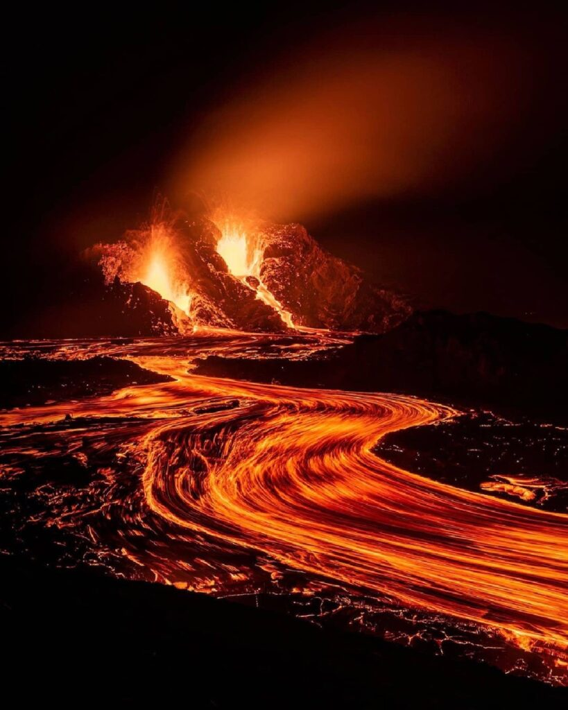 A photograph showing the active eruption from the Reykjanes Peninsular. Pictured here is the new cauldron-like cone forming around one of the main eruptive vents. Snaking away from the cone is a  glowing molten river of lava.