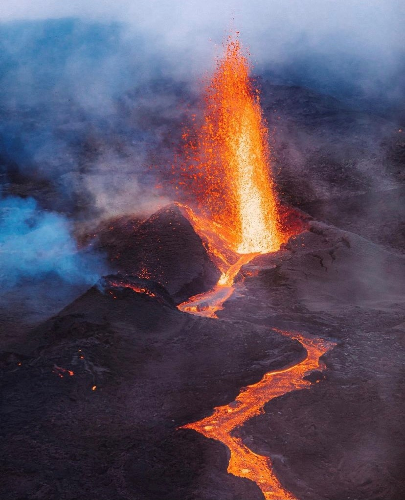 Photographed here is one of the three emission vents from Piton de la Fournaise's latest eruption. A steep-sided cinder cone has begun to build around the vent as a moderate lava fountain erupts into the air.