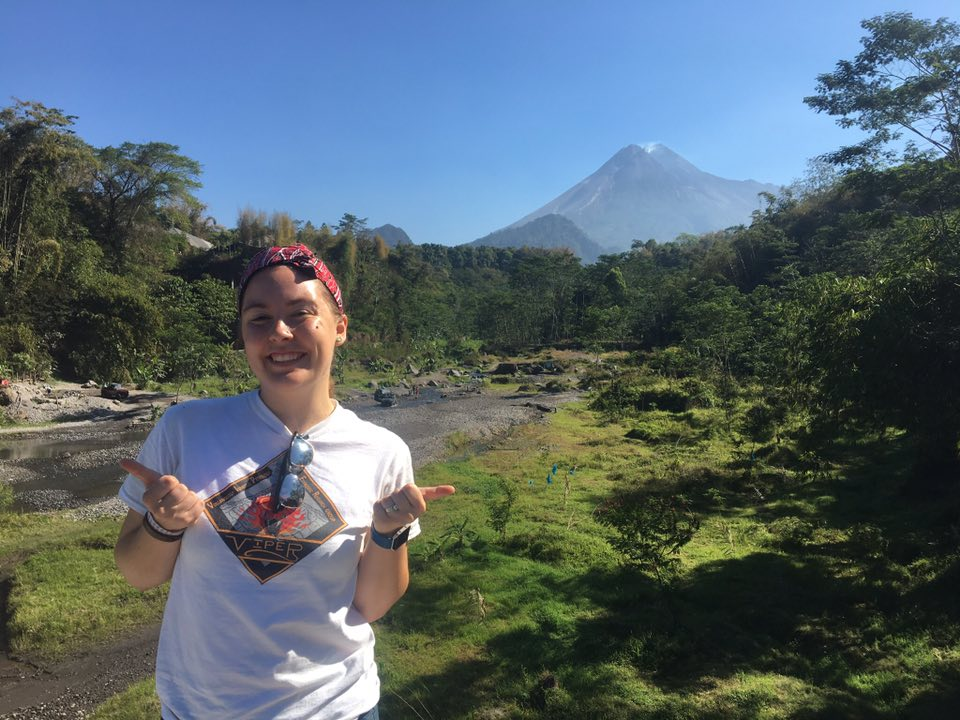 A photograph of Jade holding her thumbs up in the field. A volcano can be seen in the back ground of the image.